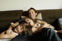 Vater spielt zu Hause mit lachenden Kindern — Stockfoto