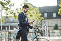 Joven empresario empujando la bicicleta, sosteniendo el teléfono inteligente - foto de stock