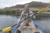 Portrait d'heureux jeune homme pagayant sur un lac — Photo de stock