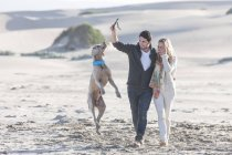 Junges Paar am Strand mit Hund — Stockfoto