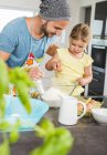 Father and daughter baking in kitchen — Stock Photo
