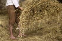 Farmer working in barn with hay — Stock Photo