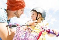 Padre cerrando el casco de la hija en bicicleta - foto de stock