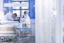 Лікарі, вивчаючи маленький хлопчик в лікарняному ліжку — стокове фото
