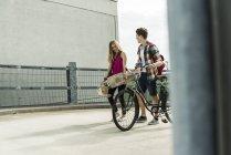 Jovem casal feliz com bicicleta e skate — Fotografia de Stock