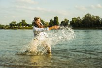 L'homme debout dans la rivière éclaboussant d'eau — Photo de stock