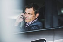 Mature businessman using smart phone in the car — Stock Photo