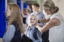 Учитель помогает школьнице с рюкзаком в коридоре — стоковое фото