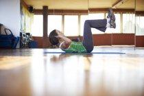 Женщина в фитнес-студии проводит тренировки брюшной полости — стоковое фото