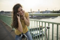 Женщина с велосипедом звонит со смартфона — стоковое фото