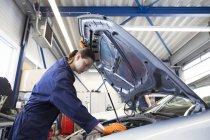 Молодая женщина работает в ремонтном гараже, проверяет двигатель — стоковое фото