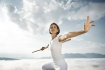 Austria, Kranzhorn, Mid adult woman exercising with fighting stick  on mountain top — Stock Photo