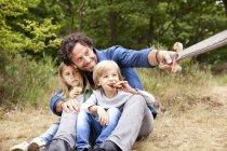 Vater mit zwei Kindern in der Natur mit Holzschwert — Stockfoto
