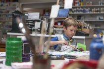 Little boy painting in an art class — Stock Photo