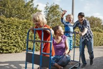 Father pushing handcart with family in allotment-garden area — Stock Photo