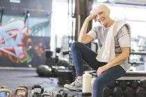 Улыбающаяся пожилая женщина в спортзале отдыхает — стоковое фото