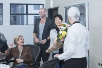 Деловая женщина получает букет цветов на случайную встречу — стоковое фото