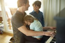 Padre che suona il pianoforte con figlia in grembo e figlio — Foto stock