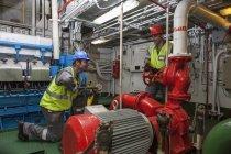 Équipage de caucasien adulte travaillant dans la salle des machines sur un bateau — Photo de stock