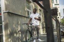 Homme avec vélo debout devant le bâtiment — Photo de stock