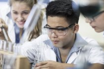 Students in chemistry class pipetting liquid into test tube — Stock Photo