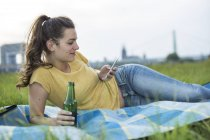 Woman with beer bottle and smartphone — Stock Photo