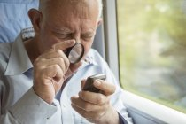Senior man reading text on a cell phone with a magnifying glass — Stock Photo