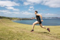 Man jogging at the coast — Stock Photo