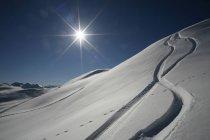 Австрия, Китцбюэль, снег с лыж отслеживает против солнца — стоковое фото