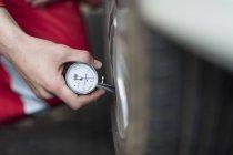 Mécanicien automobile au travail dans le garage de réparation, manomètre de pneus — Photo de stock