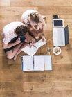Due studenti caucasici seduti sul pavimento di legno di apprendimento — Foto stock