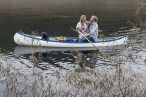 Young couple relaxing in a canoe on a lake — Stock Photo