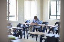 Школьник, писать в классе в школе — стоковое фото