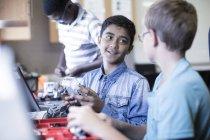 Happy schoolboys talking in robotics class — Stock Photo