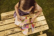 Girl drawing on a wooden magazine file in garden — Stock Photo