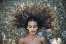 Портрет молодой женщины, лежащей на камне с взъерошенными волосами и закрытыми глазами — стоковое фото