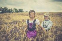 Petit garçon et fille marche dans un champ de céréales — Photo de stock