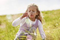 Blonde girl blowing soap bubbles on meadow — Stock Photo
