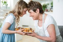 Grandmother and granddaughter in kitchen with plate of pastry at home — Stock Photo