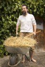 Farmer pushing wheelbarrow with hay — Stock Photo