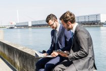 Two young businessmen sitting on wall by river, working — Stock Photo