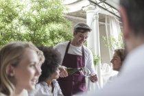 Kellner servieren Wein für Freunde zu Mittag im restaurant — Stockfoto