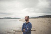 Испания, Ферроль, портрет улыбающегося человека с скрещенными на пляже руками — стоковое фото