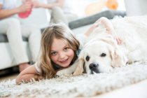 Little girl cuddling with her dog, lying on floor, parents in background at home — Stock Photo