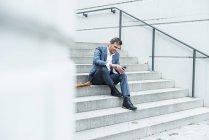 Uomo d'affari che si siede sulle scale utilizzando smart phone — Foto stock
