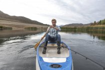 Portrait of young manwith fishing rod paddling on a lake — Stock Photo