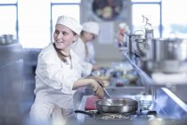 Teenage girl cooking in canteen kitchen — Stock Photo