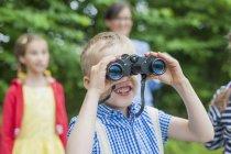 Primo piano di ragazzo con binocolo guardando in natura — Foto stock