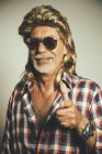 Portrait of smiling man wearing sunglasses and blond wig showing thumbs up — Stock Photo