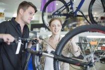 Молодий продавець і клієнт, дивлячись на велосипеди — стокове фото